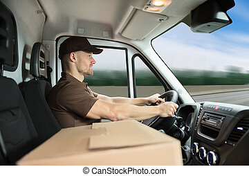 Delivery Man Sitting Inside Van With Cardboard Box -...