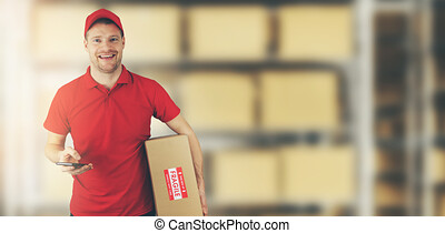 delivery man standing in warehouse holding cardboard box and mobile phone