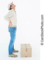 Delivery man suffering from back pain standing by box