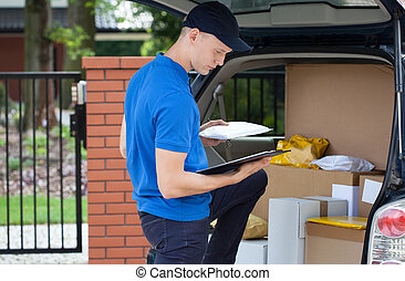 Delivery man taking package from car