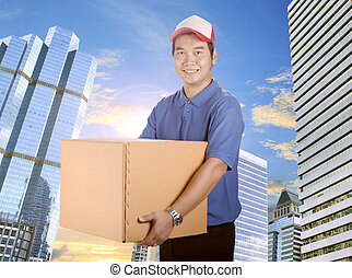 delivery man toothy smiling face and holding card box delivering in city building