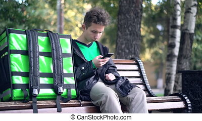 delivery man with green backpack awaiting the order for ...