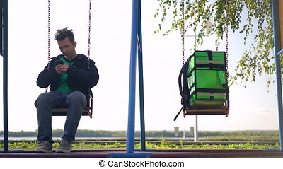 delivery man with green backpack awaiting the order for delivery on the swing.