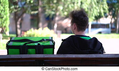 delivery man with green bagpack awaiting the order for delivery.