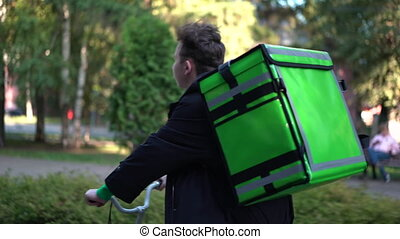 delivery man with green bagpack rides a bicycle through the ...