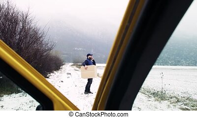 Delivery man with smartphone delivering parcel box to recipient.