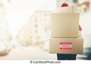 delivery man with stack of boxes standing on the street. copy space