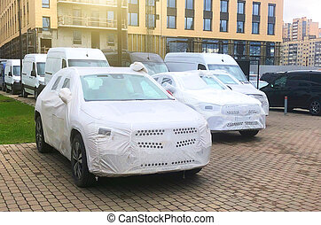 Delivery of new cars covered in white protective covers, car parking.