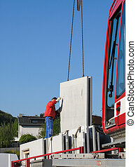 Unloading of parts of a prefabricated house with a crane by a construction worker.