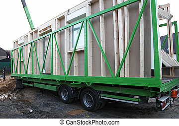 Delivery of the various sections of a prefabricated wooden house witth the exterior walls loaded onto a long bed industrial trailer for transportation