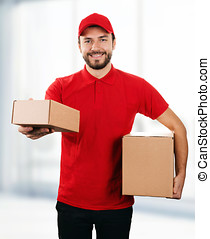 delivery service - young smiling deliveryman with cardboard boxes