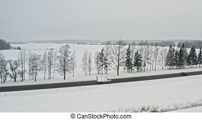 Delivery van driving on winter country road, aerial view ...