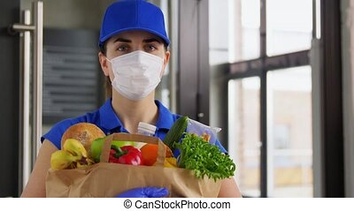delivery woman in face mask with food in paper bag - health ...