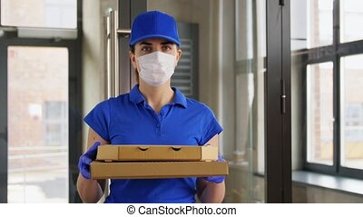 delivery woman in face mask with pizza boxes