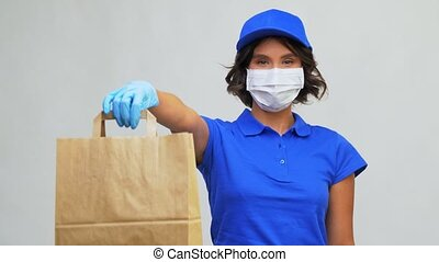 delivery woman in mask holding paper bag with food - health ...