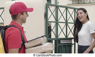 Deliveryman bringing packages to customers door, ringing doorbell. Woman confirming receiving parcel on tablet. Shipping or delivery service concept