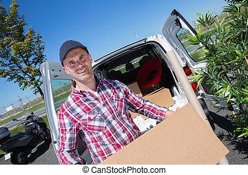 deliveryman, proceso de llevar, un, cartón, paquete, caja, delante de, entrega