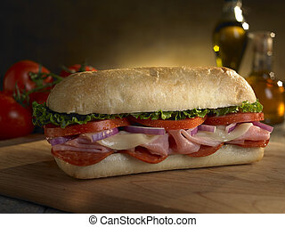 Foot long deli sub sandwich on a cutting board with tomatoes in the background