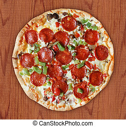 Cooked frozen deluxe pizza with pepperoni, red onion, red pepper, green pepper, mushroom and shredded mozzarella cheese on wood background.