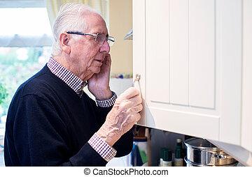 demente mens, vergeetachtige man, het kijken, senior, kast, thuis
