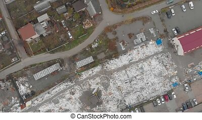Demolished buildings houses aerial drone top birds eye view city cars traffic road overhead camera movement
