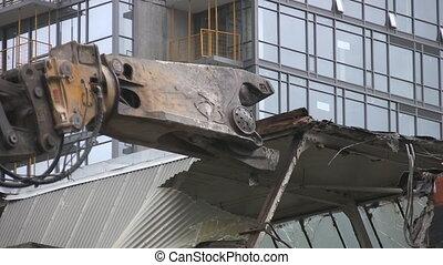 Demolition. - Hydraulic arm with claw, demolishing a city...