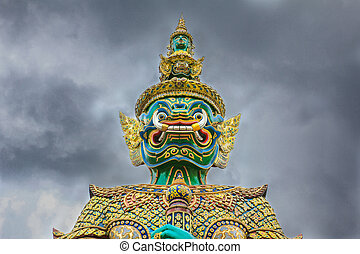Demon Guardian with cloudy sky at Wat Phra Kaew , The Temple of Emerald Buddha in Bangkok, Thailand