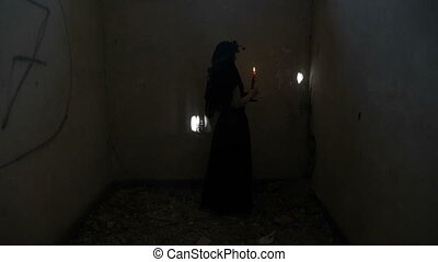 Demonic gothic evil woman turning around holding a candle...