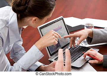 Demonstration - Woman and man pointing at the monitor of...