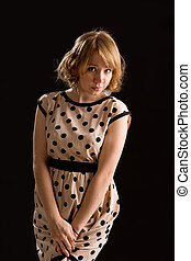 Demure young woman in a polka dot dress