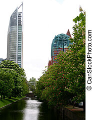 Modern buildings in Den Haag (The Hague) with canal and flowered trees in foreground