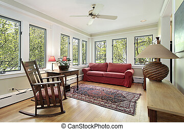 Den in suburban home with wall of windows