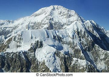 Denali Peaks Under Blue Sky - Rugged snowcapped mountain...