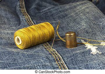 Denim fabric with needle, thread and thimble