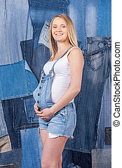 Denim for pregnant women. Side view of beautiful pregnant woman in jeans clothes holding hands on her abdomen while standing against jeans background