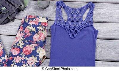 Denim handbag and blue top. White footwear and floral pants....