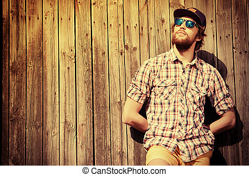 Handsome modern young man standing near a wooden fence. Fashion.