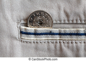 Denmark coin denomination is 1 krone (crown) in the pocket of beige denim jeans with blue stripe