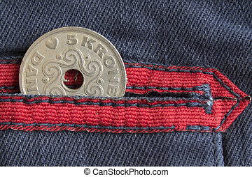 Denmark coin denomination is five krone (crown) in the pocket of worn blue denim jeans with red stripe