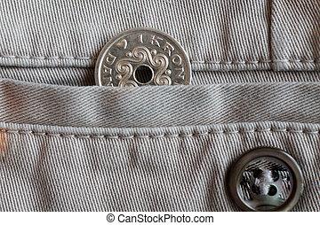 Denmark coin denomination is one krone (crown) in the pocket of beige denim jeans with button
