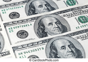 Denominations of one hundred dollars, located on a diagonal, close-up. Franklin winks.