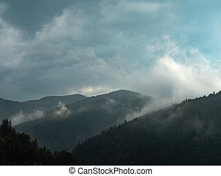 Dense rainy clouds above the hillsides at summer....