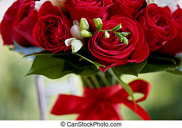 dense red bouquet of roses, tied with a ribbon.