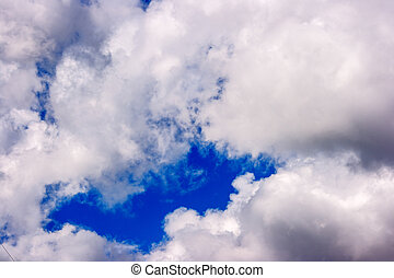 dense white clouds on a beautiful summer blue sky