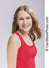 Dental and Medical Concept. Smiling Caucasian Young Blond Teenage Girl With Teeth Bracket System. Against White Background.