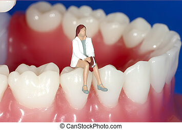 Miniature Woman Sitting on Teeth