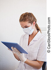 Dental assistant working on tablet pc