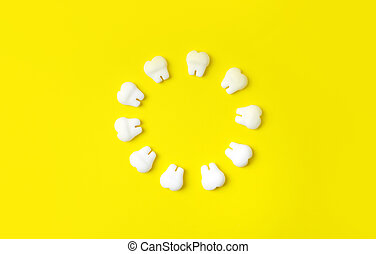 Dental background. Teeth models making round on a yellow background. Copy space.