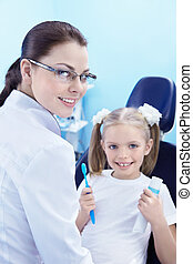 Dental care - A child in a dental chair with a toothbrush...