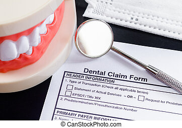 Dental claim Form with model tooth and dental instruments.